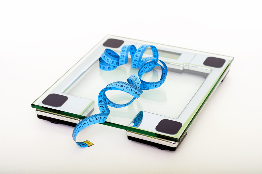 Photo of clear glass scale with blue measuring tape laying on top of it to show how stress causes weight gain