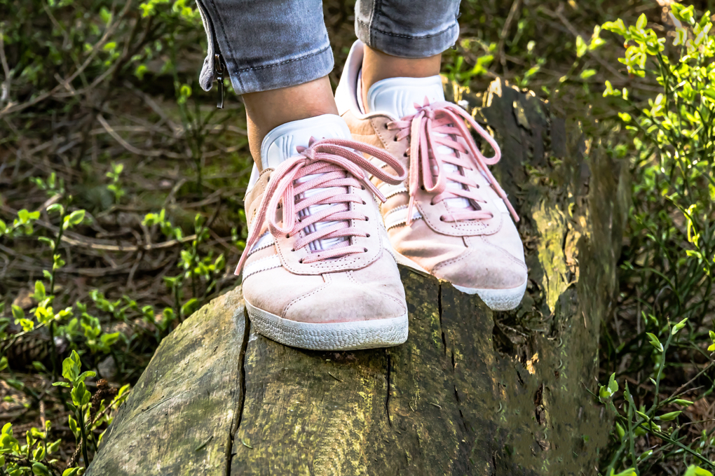 Photo of pink sneakers on feet that are walking on a fallen tree taking steps toward getting started on a healthier lifestyle