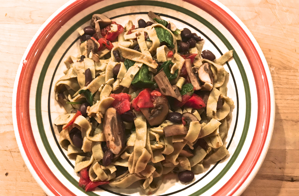 Photo of vegetarian black bean pasta in a colorful bowl as a healthy main meal