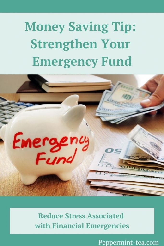 Photo of white piggy bank with emergency fund written on it in red ink beside stacks of money