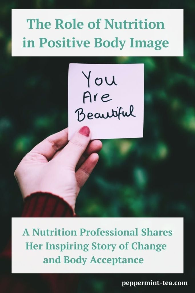 "Photo of a woman's hand holding up a sticky note saying ""You are beautiful"" as an example of positive body image"