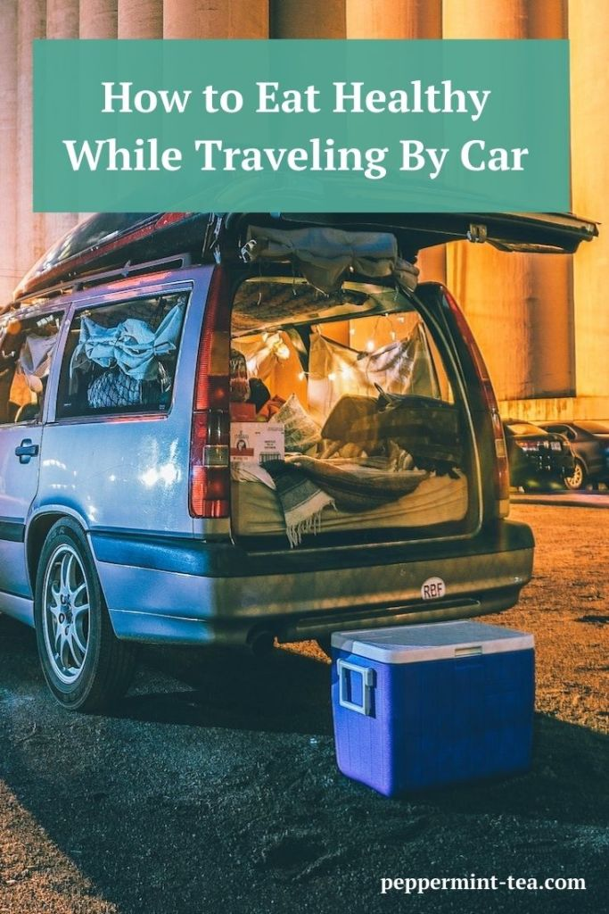 Photo of car with cooler sitting beside it as example of how to eat healthy while traveling
